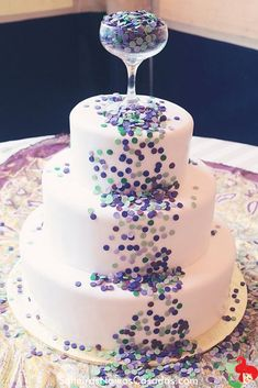 """Purple, blue, and teal edible confetti dots spill out of a champagne glass topper down this otherwise simple white wedding cake. Such a fun idea! Love that they sprinkled more of the """"confetti"""" onto the display table for continuity. Pretty Cakes, Cute Cakes, Beautiful Cakes, Amazing Cakes, Confetti Cake, Wedding Confetti, Glitter Confetti, Gold Glitter, Super Torte"""