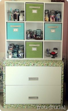 A craft hutch from an old lateral file cabinet, Mod Podged with fabric and a 9-cube shelf on top.