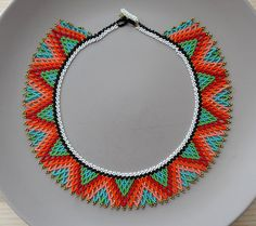 Color: Green, teal, red, orange, salmon, black, white, bronze Size: 19 x 1.25 48.2cm x 3.25 cm  Beaded toggle clasp  > Handmade with love and care  This is a really fun and colorful choker. ideal for add a ethnic bohemian touch to your look. I made it with special attention to details and you can see it in the brooch and the bronze tips.  Ethnic with contemporary twist  For my pieces I initially was inspired by the work of Mexican and Native North Americans. However, my style has evolved…
