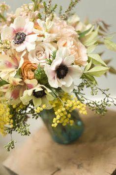 Anemones, roses, ranunculus, minosa, alstroemeria, seeded eucalyptus.  peach yellow and cream