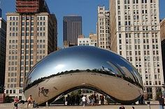 A large, highly-polished, mirrored bean-shaped sculpture seen from the east, reflecting the skyscrapers to the north along East Randolph Street (The Heritage, Smurfit-Stone Building, Two Prudential Plaza, One Prudential Plaza, and Aon Center. Chicago!