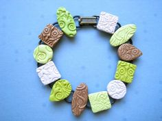 "The sale in my Etsy shop continues today until June 8th. 20% off your order when you use the coupon code ""Spring"". Lots of fun clay bracelets available, like this one in shimmery shades of green, tan and white."