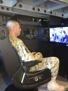 """Check out the soldier using a Play Station 3 (PS3) game console donated by Omni Financial to the USO to help our soldiers. The gamer shown is seated at a one of four game stations inside a remolded UH-1 """"Huey"""" helicopter positioned in the center of the FT. Campbell USO facility. Enjoy!"""