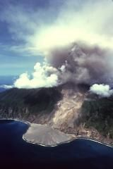 A diffuse ash column rises above the summit of Soufrière Hills volcano on April 2, 1997. The prominent delta seen in this aerial view from the NE was created by pyroclastic flows that descended to the eastern coast down the Tar River valley. The pyroclastic flows were produced by periodic collapse of a lava dome growing in the summit crater, which is breached to the east. The eruption began in July 1995
