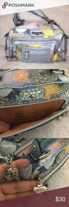 Authentic Kathy Van Zeeland Purse Baby blue, lilac purple, navy blue, yellow, orange and white. Beautiful floral print. Embossed leather trim. Bold silver hardware. Compartments for credit cards in front outside zippered pocket and inside purse. Zippered pocket inside. 3 additional small zippered pockets outside purse. Super cute. Minor wear and tear. Kathy Van Zeeland Bags Mini Bags
