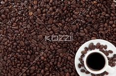 coffee beans and coffee cup. - Close-up shot of baked coffee beans and coffee cup with black coffee.