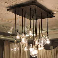 Idea: Use regular bulbs and buy lamp kits and hang them at different heights through a piece of wood stained and drilled. Unsure if this is realistic or not, but a cool idea.