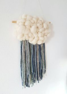 Follow me on Instagram for shop updates and new styles @studioversie A lovely hanging, perfect as a nursery gift. A fluffy cloud with colorful fringe. A lovely mix of color. A fringe of blue, grey and a touch of gold. The cloud is made out of an ivory roving. The hanging is made out of beautiful quality, merino roving and wool. The piece meassures app 37 cm by 21 cm -8 inch in width by 14 inch in length. It is hung from a wooden dowel. Other colors are of course possible! Check out my…
