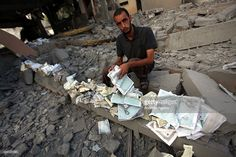 A Palestinian man collects copies of the Quran, Islam's holy book, in the rubble of Omar Ibn Abd al-Aziz mosque destroyed in an Israeli air strike in the northern Gaza Strip town of Beit Hanoun on August 25, 2014. At least 2126 Palestinians have been killed, more than 10,860 others injured and 100 mosques have been damaged in relentless Israeli attacks on the Gaza Strip since hostilities began on July 7.