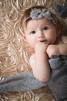 petite fille en gris sur un plaid a fleur beige.