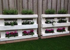 Saaie schutting opgevrolijkt met frisse pallets en planten.