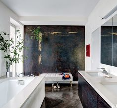 An abstract mural by Surface & Architecture Workshop distinguishes the master bath of jewelry designer Ippolita Rostagno's Brooklyn brownstone; the tub and sink fittings are all by Dornbracht, and the tufted bench is by RH | archdigest.com