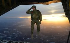 A U.S. Soldier assigned to 1st Battalion, 10th Special Forces Group (Airborne) salutes his fellow Soldiers while jumping out of a C-130 Hercules aircraft over a drop zone in Germany, Feb. 24, 2015. (U.S. Army photo by Visual Information Specialist Jason Johnston)
