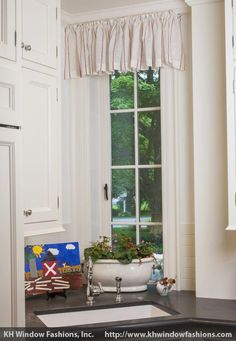 A simple valance for a tall and thin casement window in a convenient corner.  Let the light and breeze in and keep your view out. Room designed by F.D. Hodge Interiors