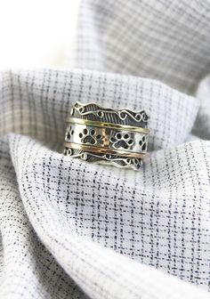 Give your fidgety fingers the paw treatment with our whimsical ring, encircled by a trio of metals. A brass and copper outer layer of paw prints spins freely around an accented ring, centering your mind on your love for animals! #TheAnimalRescueSite