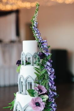 Mischief Maker Cakes I Purple Sugar Flower Fairytale Wedding Cake with Foxgloves, Ranunculus, and Ferns I Gothic Architecture Wedding Cake #mischiefmakercakes #themischiefmaker #sugarflowers #sugarflowerweddingcake #purplewedding #purplecake #fairytaleweddingcake #gothicarchitecure #fairytalewedding #luxuryweddingcake #kentucky #kentuckyweddings #magicalweddingcake #disneyinspired #disneywedding #kentuckyweddingcakes #bemischievious