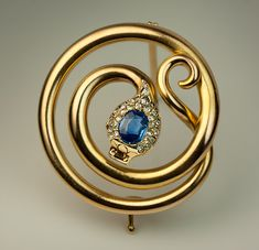 A Stylish Antique Russian Victorian Era Late 1800s Snake Brooch Pin, St. Petersburg, 1882-1898, maker's initials 'XB'. The 14K gold brooch is designed as a stylized coiled snake, the head embellished with a blue sapphire surrounded by numerous rose cut diamonds.
