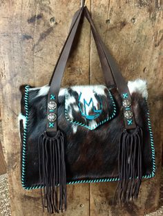 The Buckaroo Tote, with suede lined side pockets, D loop fringe on the straps, and the owners brand on the flap in turquoise suede. gowestdesigns.us