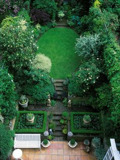 Oval, orderly English garden with symmetry, terrace, brick herringbone path, containers and privacy