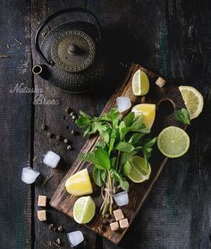 Ingredients for Ice Green Tea - Ingredients for ice green tea lime, lemon, mint, sugar, green tea and ice cubes on wooden chopping board with black iron teapot over old wooden background. Rustic style. Flat lay