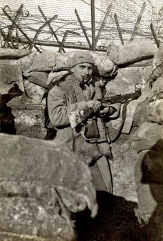 History in Photos: World War I. In Argonne. A marksman in his trench at his view hole smoking his pipe.