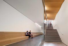 Il design etereo di Shigeru Ban è visibile in questa immagine: pareti total white contrapposte alla texture della panca in legno che corre lungo tutto il corridoio