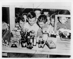 CHILDREN WAITING TO BUY AT A FIREWORKS STAND: Kids are pointing at what they want through a wire barrier. Minneapolis Tribune 7/2/39