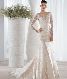 This elegant all lace modified A-line gown features magnificent lace appliques over a natural illusion throughout long sleeves and dramatic low back with button closures.  Back features a Chapel train.
