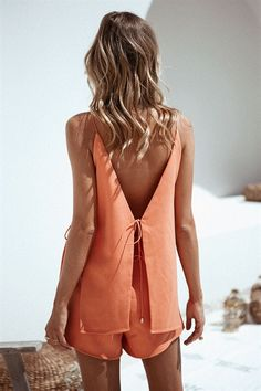 Treat your wardrobe to some colour with the Valencia Playsuit, made from a thick fabric in an orange hue. It is an overlay style playsuit and features ties at sides, a V neckline and split open back. Complete the look with a black hat and slides! By Sabo Skirt.