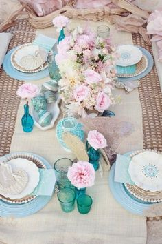 Ocean tablescape.  Layers of blue and cream plates worn blue napkins.  Seashells adorn the table.  #tablescape