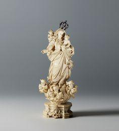 Importante Nossa Senhora com o Menino Jesus, escultura Indo-portuguesa, do séc. XVIII, em marfim. A figura está representada de pé, sobre nuvens, com sete cabeças de anjos aladas aos pés, assente sobre peanha de formato arquitectónico decorada com três flores josefinas. Usa longos cabelos dispostos em madeixas sobre os ombros e costas. Enverga túnica comprida até aos pés, com véu, manto e sobre-túnica, dispostos em pregueados assimétricos criando um efeito esvoaçante. Tecidos ricamente…