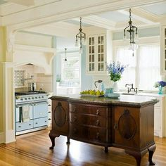 Using an old piece of furniture as center island. Not such curvy legs but mix dark wood into painted elements of kitchen
