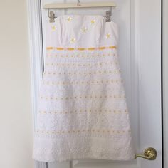 Lilly Pulitzer Strapless Dress Strapless white dress with yellow ribbon and embroidery. This dress is stunning and in excellent condition. One small spot in the middle of a flower on the back but not noticeable unless you are looking. I would keep if it fit me!  Lilly Pulitzer Dresses