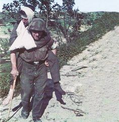 German soldier carries a wounded comrade.