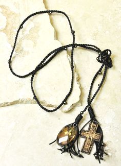 Transformation (TS6205041104) Almost 30 naturally metallic colored pearls are intertwined in this dark brown leather-cord braided lariat necklace.  The amber-hued crystal pendant shines brilliantly in the presence of light, making it the perfect balance for the hanging crucifix on the opposite end. Gorgeous!