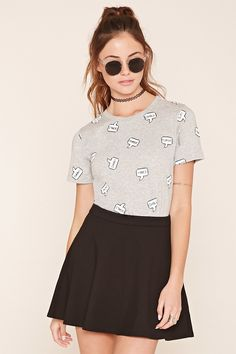 """A heathered knit tee featuring a ribbed neckline, short sleeves, and an allover """"Turnt Goals Chill Shade Vibes Slay"""" graphic."""