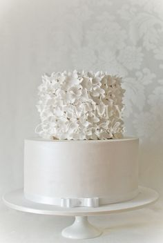 white wedding cake. ruffled top, simple bottom layer with bow