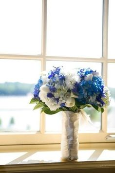 Bridal bouquet comprised of white tulips, light and dark blue hydrangea, white mini callas, white stock, blue delphinium and blue triteleia (the tulips to celebrate dear partner's Dutch heritage). The bouquet is bound in satin ribbon and decorative pins.