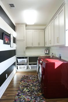 laundry room with black and white stripes wall, red washer and dryer, leather strip rug, gray greige cabinets, gold appliance hardware, basket storage