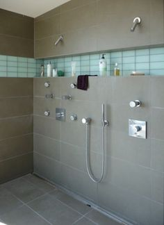 The only thing that I don't like about this shower is that it's side by side. Love the way they did the cubby all the way along the wall above the shower controls. I like the grey tile overall with the ribbon of light color tile..