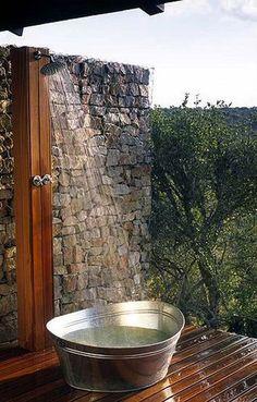 Douche d'extérieur installée sur mur pierres du jardin