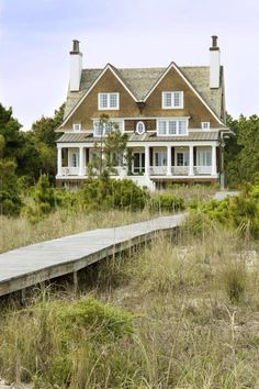 HOME DECOR – COASTAL STYLE – a seaside home with a small boardwalk leading to sand dunes and the beach.
