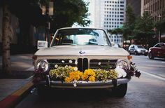 """Lovers of all things vintage, their BMW was decked out by the sweet bridal party with flowers, tin cans, yarn pompoms, and """"just married"""" lettering. Photo by Benj and Maddie Haisch Just Married Car, Flower Car, Wedding Car, Wedding Wishes, Bridal Car, Wedding Bells, Diy Wedding, Once Wed, Green Wedding Shoes"""