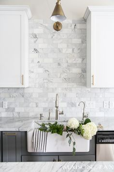 Gray and white cabinets, marble subway tile, Carrara countertops, and brass hardware