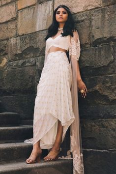 Ivory and gold brocade dhoti skirt with leather crop top & net embroidered cape. Estimated shipping: weeksCare instructions: Dry clean only Indian Fashion Dresses, Dress Indian Style, Indian Gowns, Indian Designer Outfits, Indian Attire, Fashion Outfits, Indian Wear, Fashion Fall, Modern Fashion