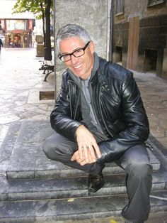 Silver Fox with glasses and leather jacket stooped on grey marble…
