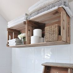 Wooden crates on a bathroom wall holding towels and candle