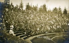 The faded glory of Shively Park - This postcard shows the grand opening of Astoria's centennial at a stadium and amphitheater built for the celebration and pattered after the University of California's Greek Theater. The line of people at the top are standing on the road. The wooden stairs and seats no longer exist.