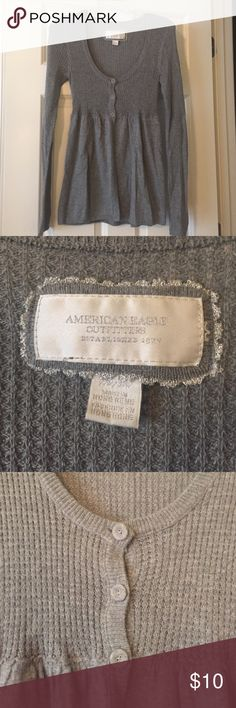 American Eagle Sweater in Medium This gently used American Eagle sweater is gray and is in a size medium. The sweater has three buttons and then the fabric splits and there is an opening. American Eagle Outfitters Sweaters V-Necks