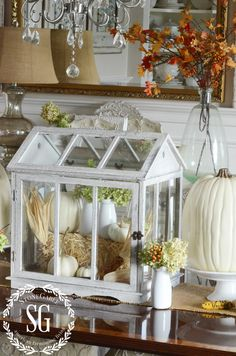 Pretty, muted fall décor - white pumpkins on cake pedestals, white vases with hydrangea and orange berries, window greenhouse filled with a small hay bale, Indian corn, and white pumpkins, burlap runner